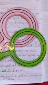 Two cut out cardboard magnifying glasses sit on a page of child's schoolwork.